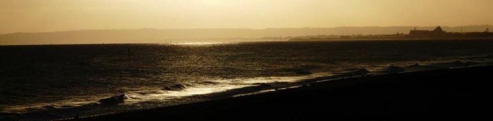 La plage de Lion sur Mer sous les lumières tamisées du soleil levant.